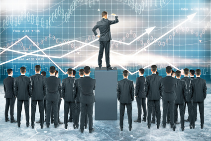 Businessman standing on pedestal and looking into the distance with other businesspeople around on forex chart background. Leadership concept